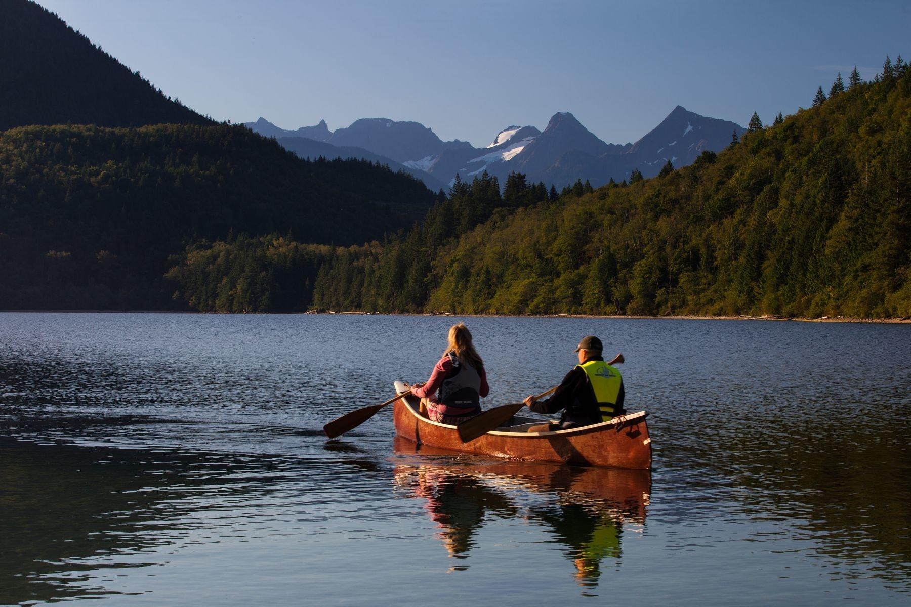 Two person canoe on lake with mountains in background