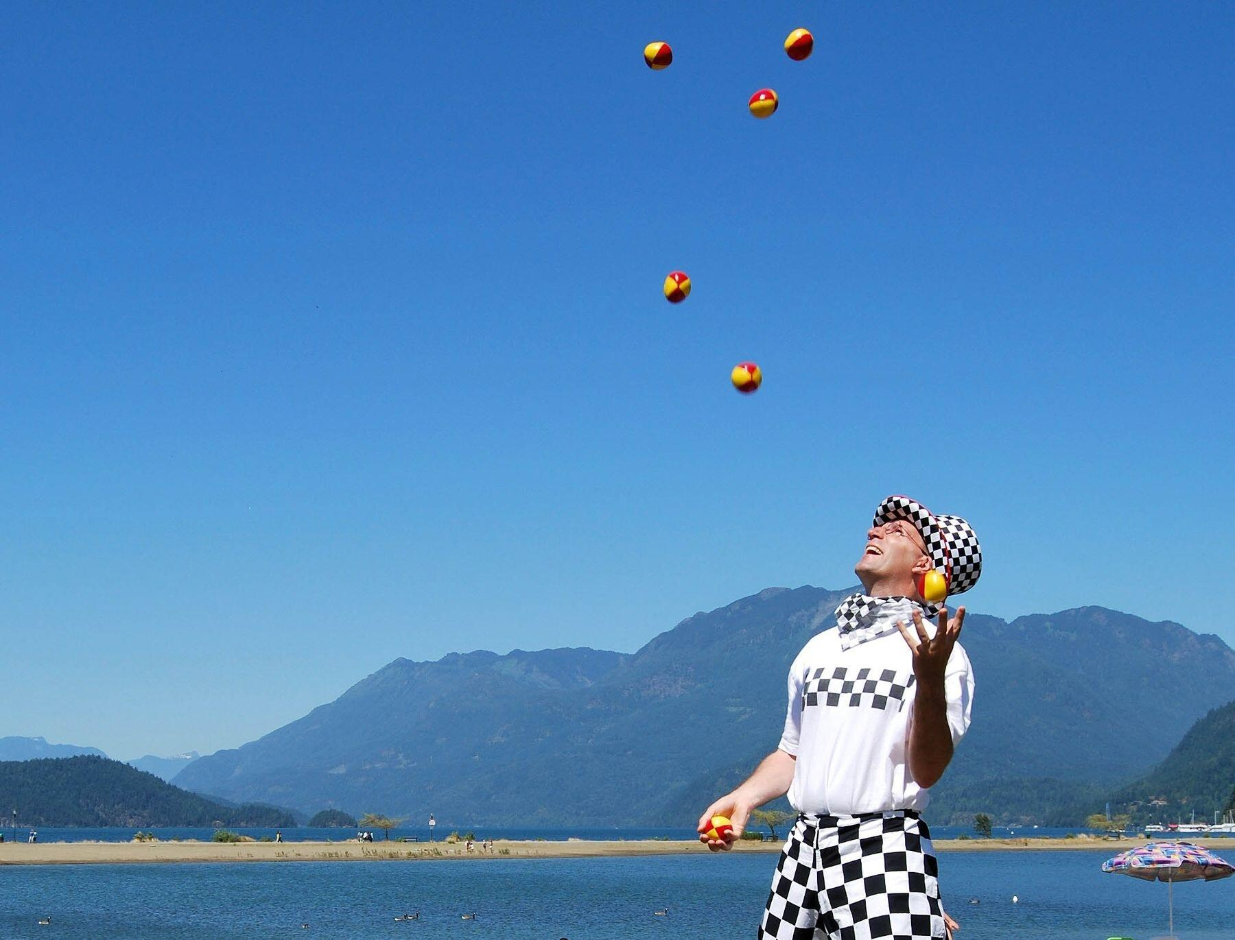 Man in checkerboard pants and hat juggling