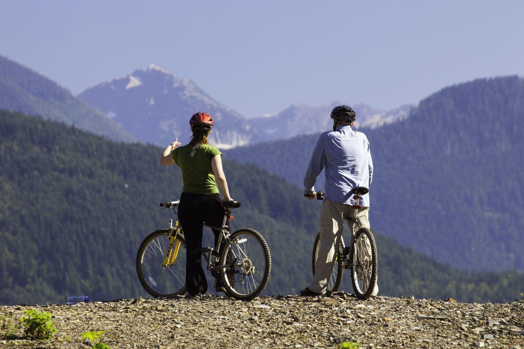Two people on mountain bikes with mountain views