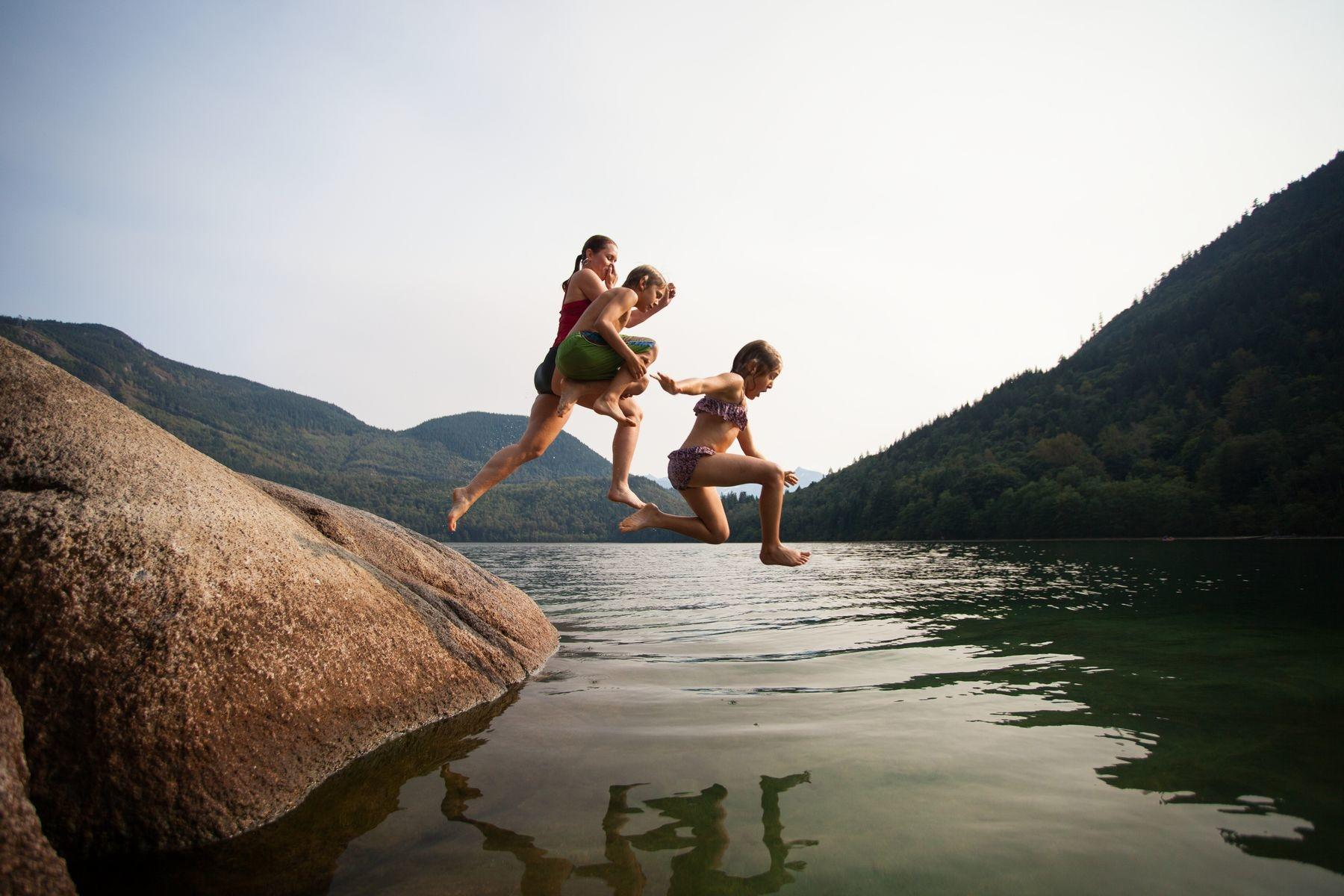 Three children jumping into lake