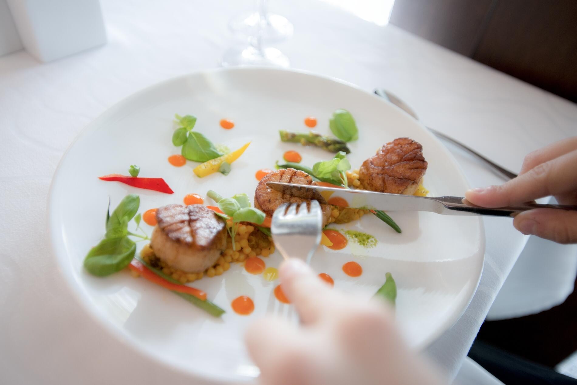 Guest cutting plate of seared scallops