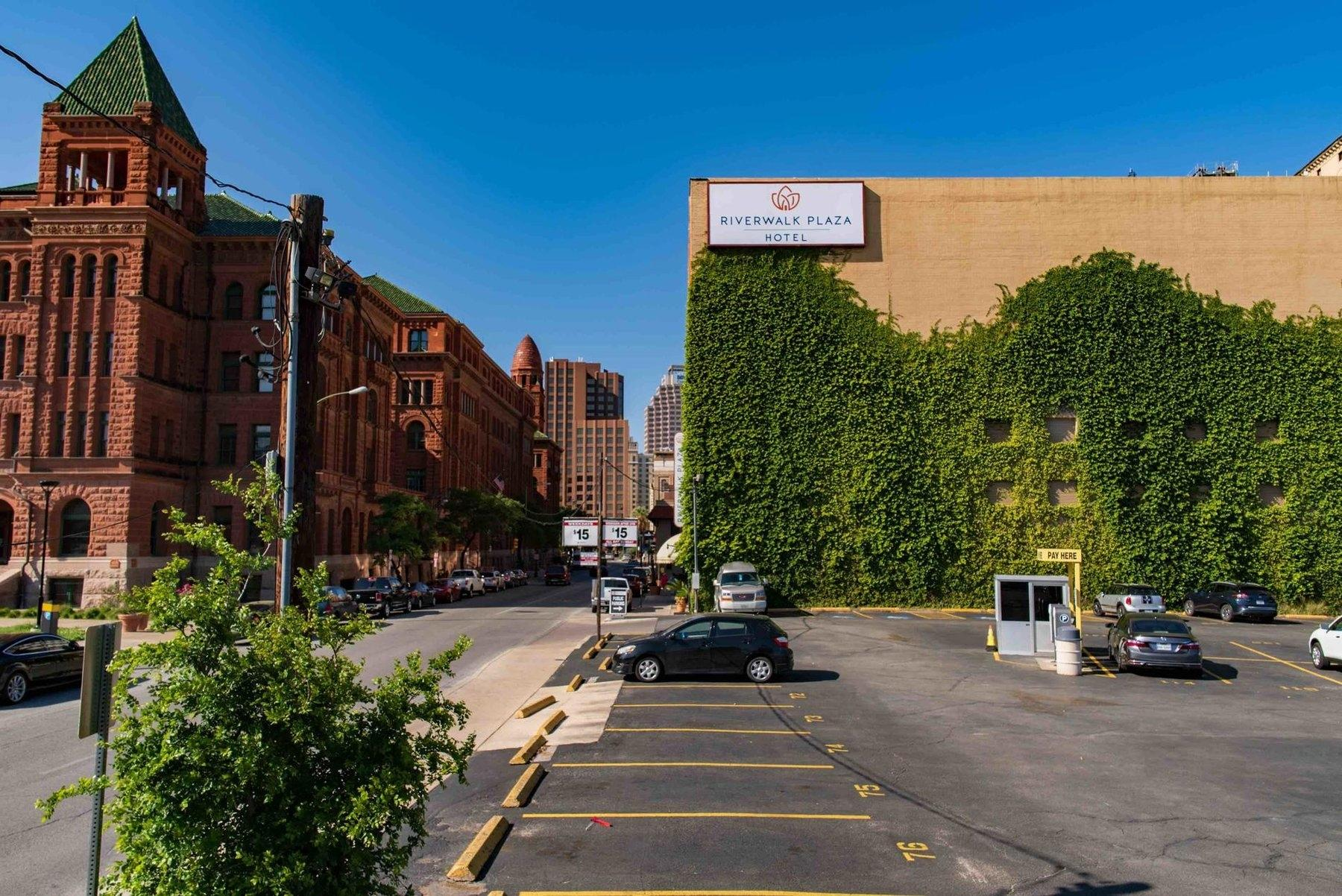 Parking lot and hotel exterior wall covered in ivy