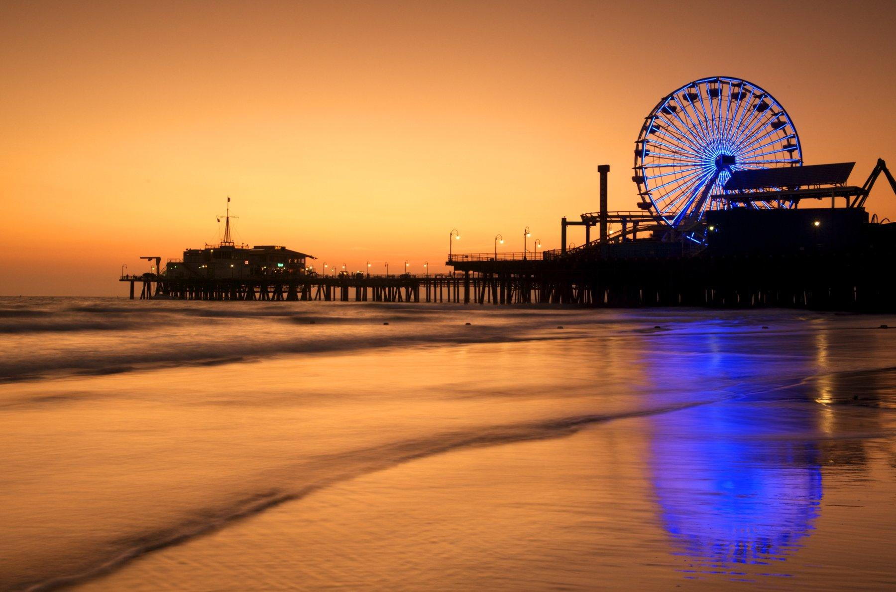 Santa Monica Pier lit up at sunset