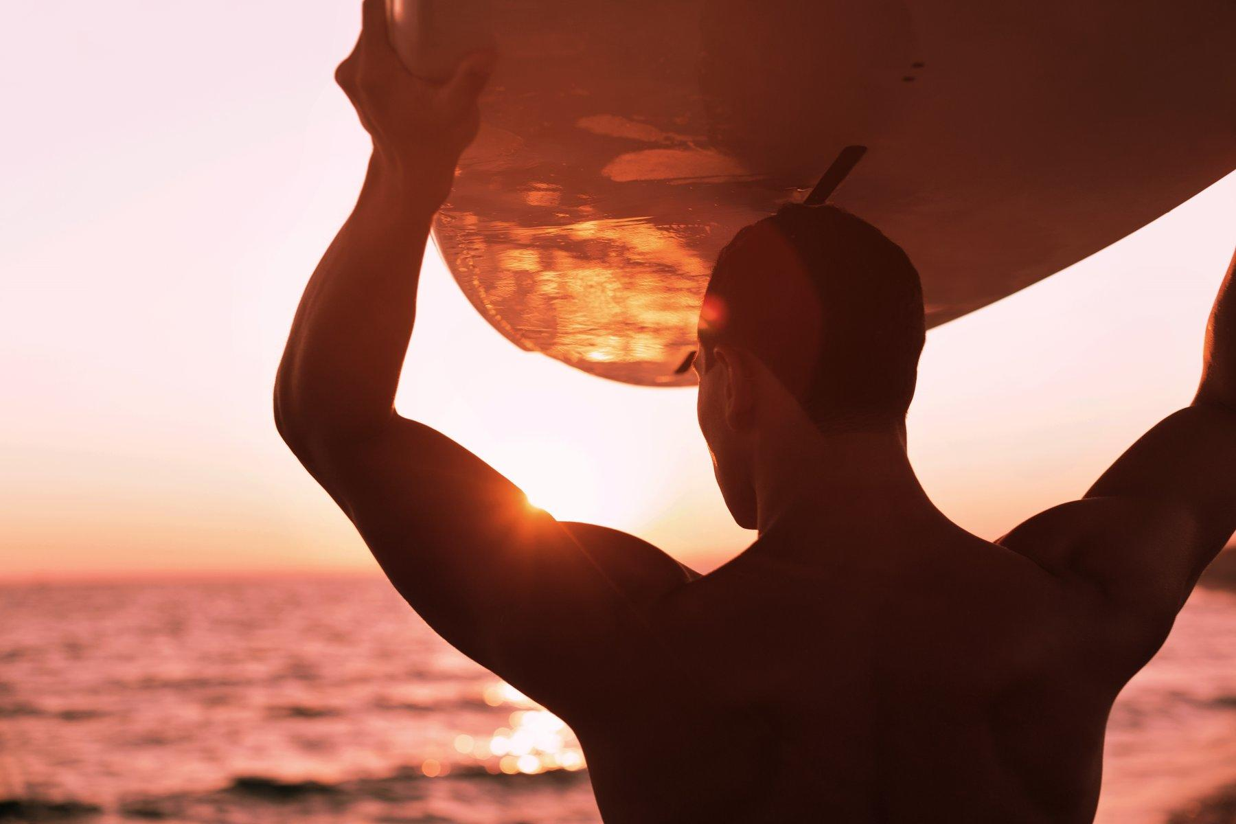 Close photo of man carrying a surfboard