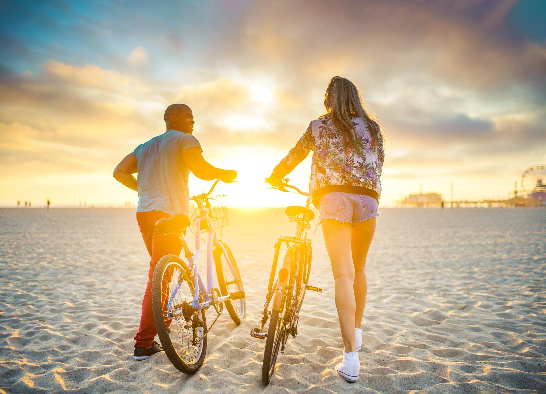 Two friends walking their bikes through the beach sand
