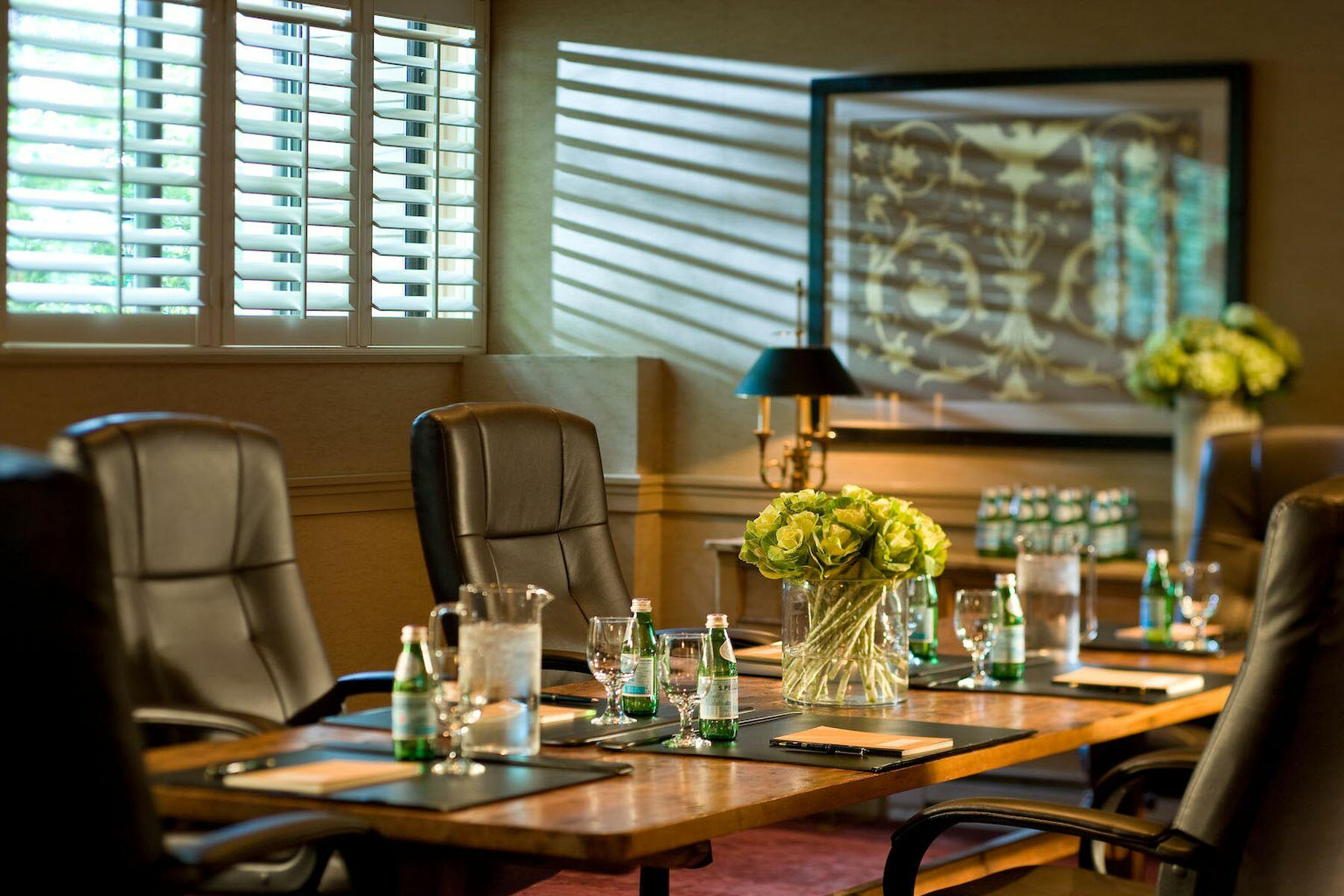 Small, well-lit conference room with long table.