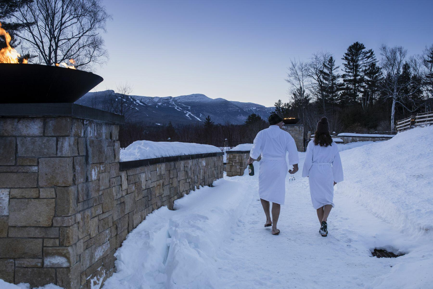 Couple walking in the Vermont snow in white bathrobes.