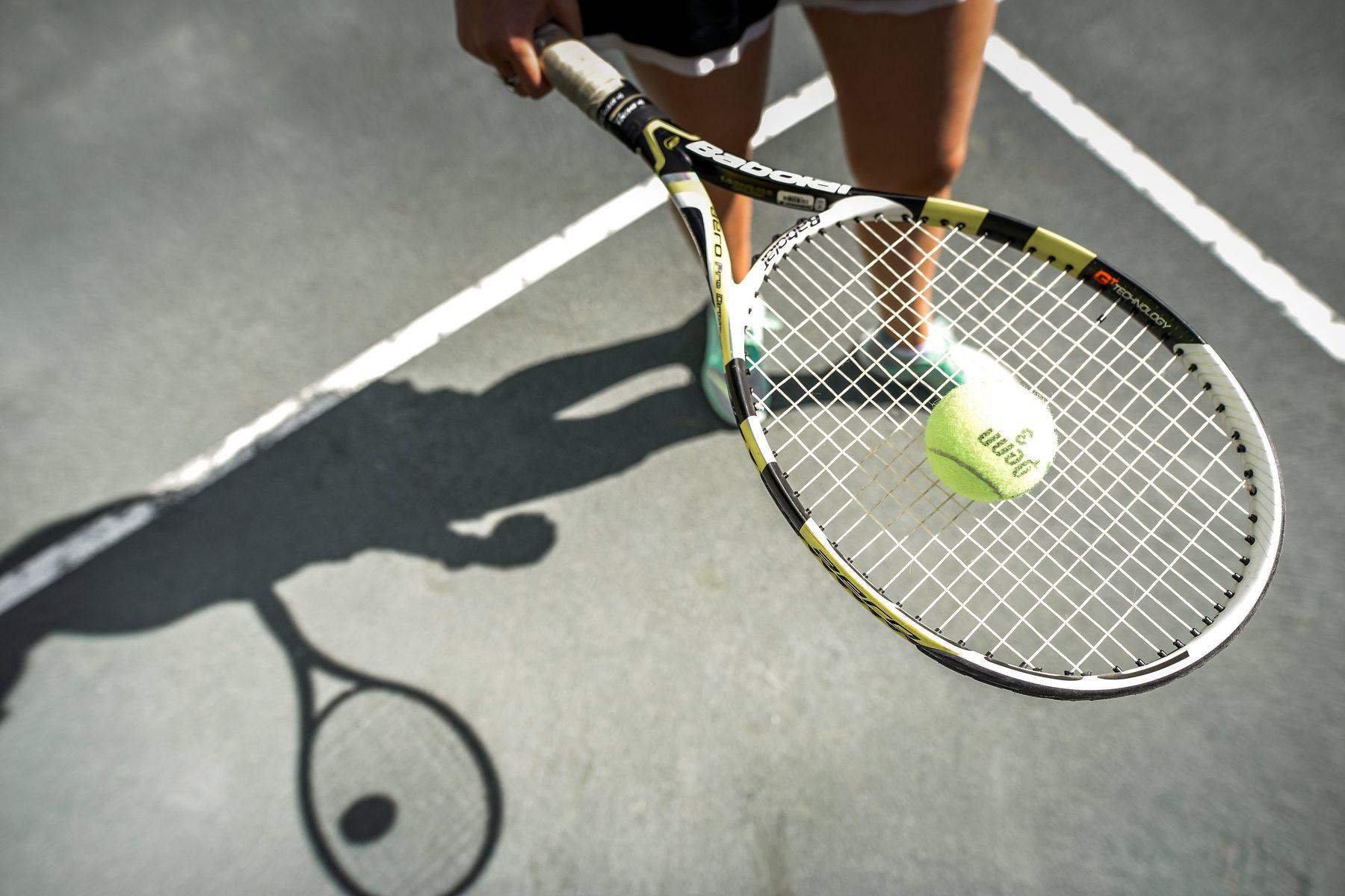 Close photo of tennis ball resting on a racquet.