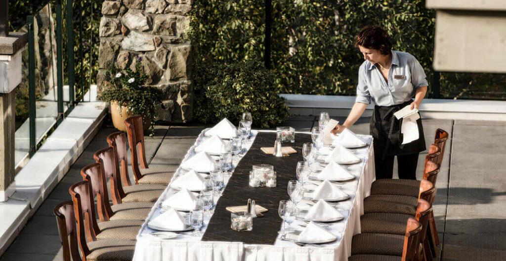 waitress setting up dinner table for wedding