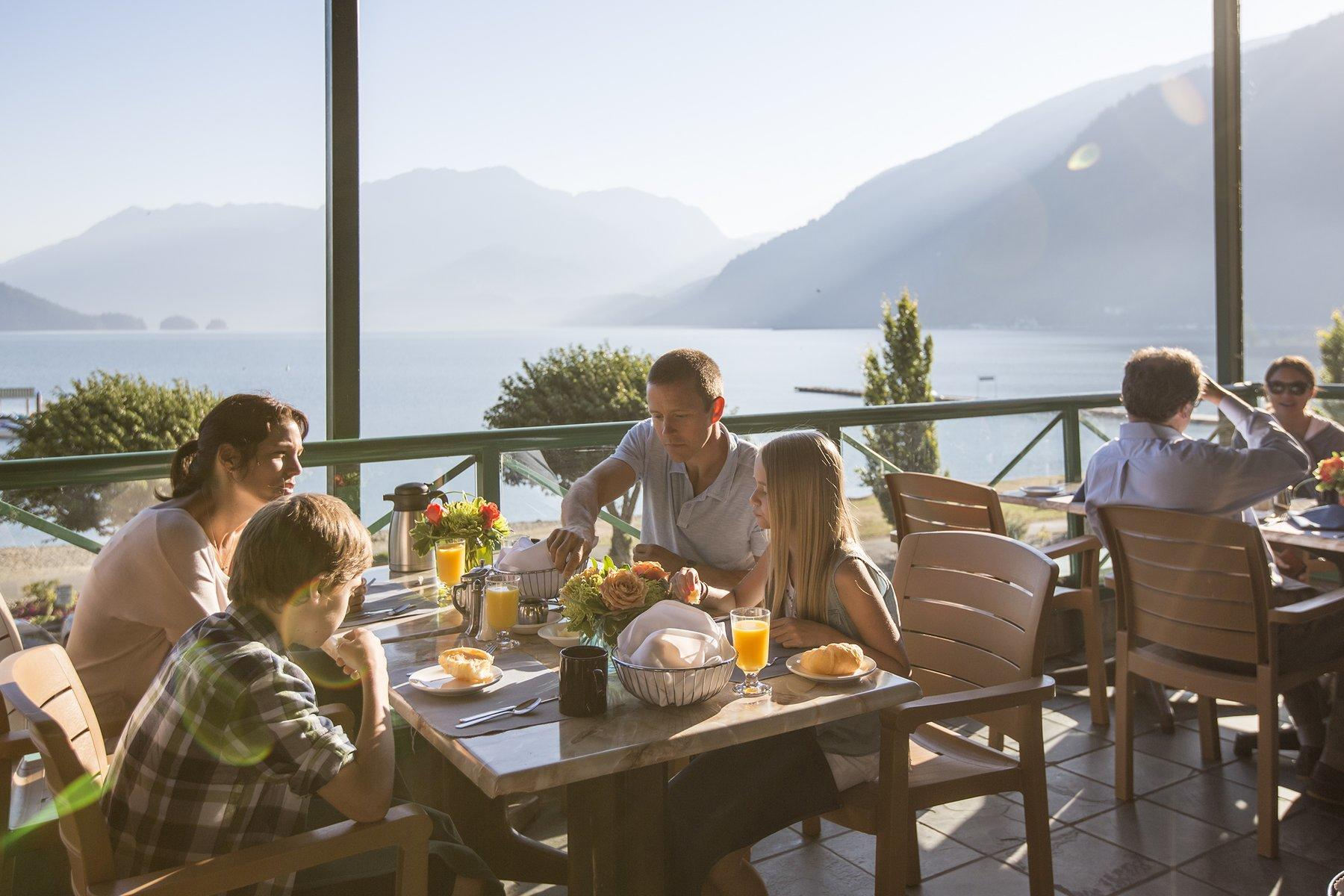 Family eating at outdoor restaurant with mountain and lake views