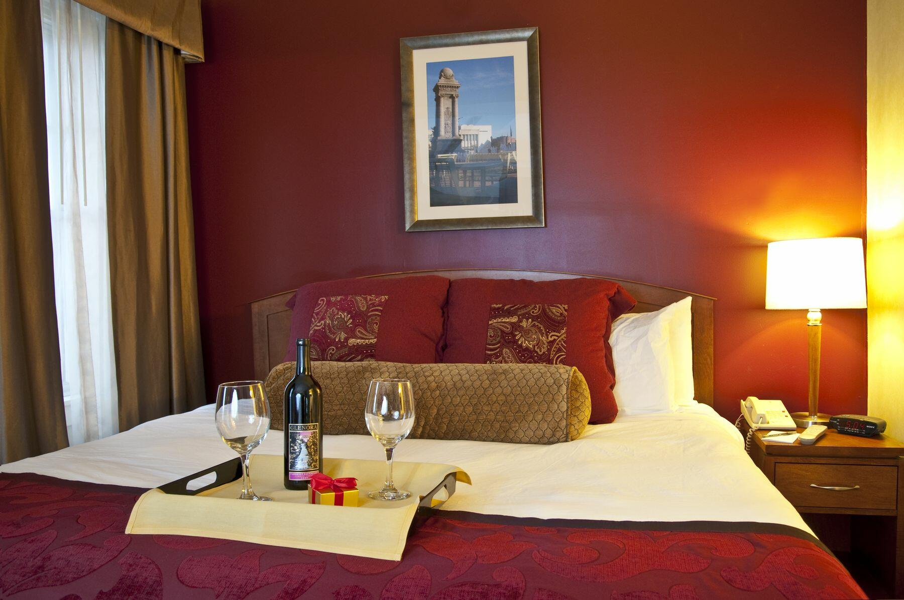 Tray with bottle of wine and glasses on bed