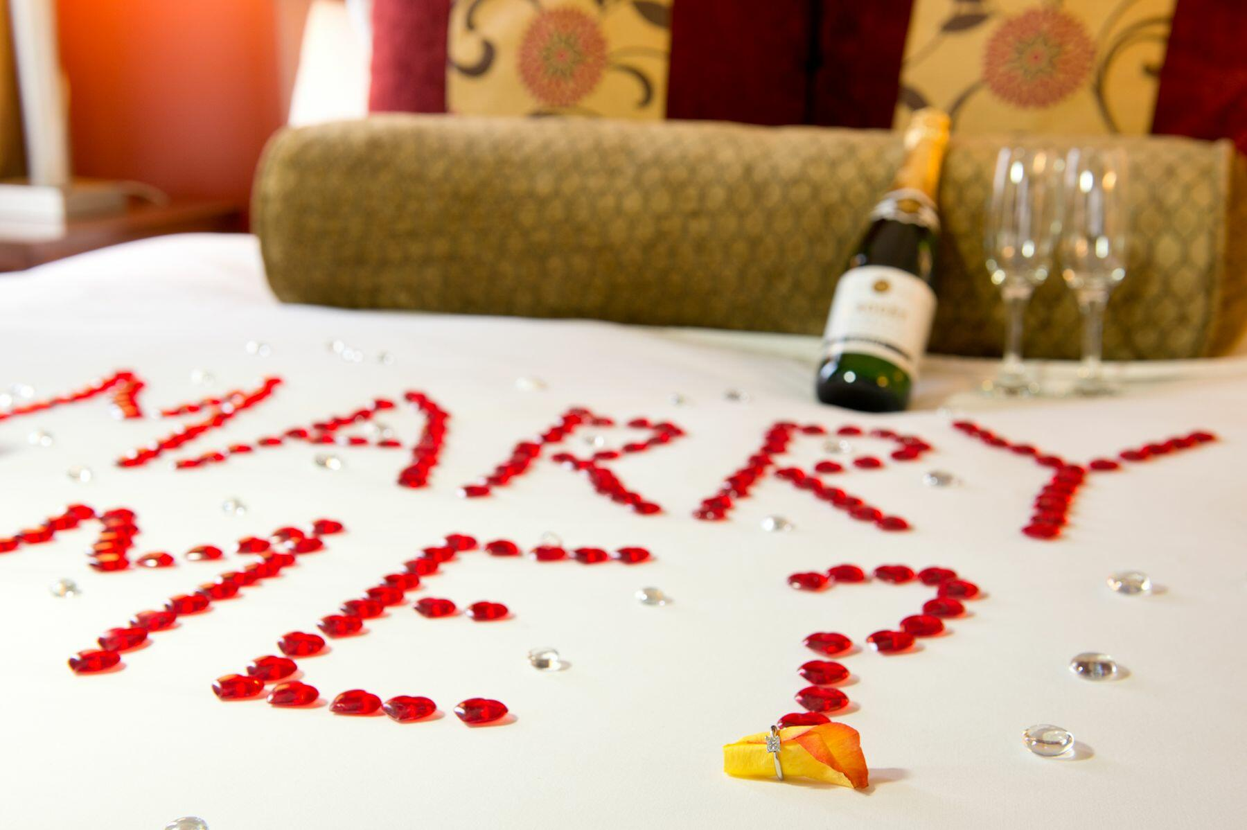 Marry Me? written out in rose petals on bed.