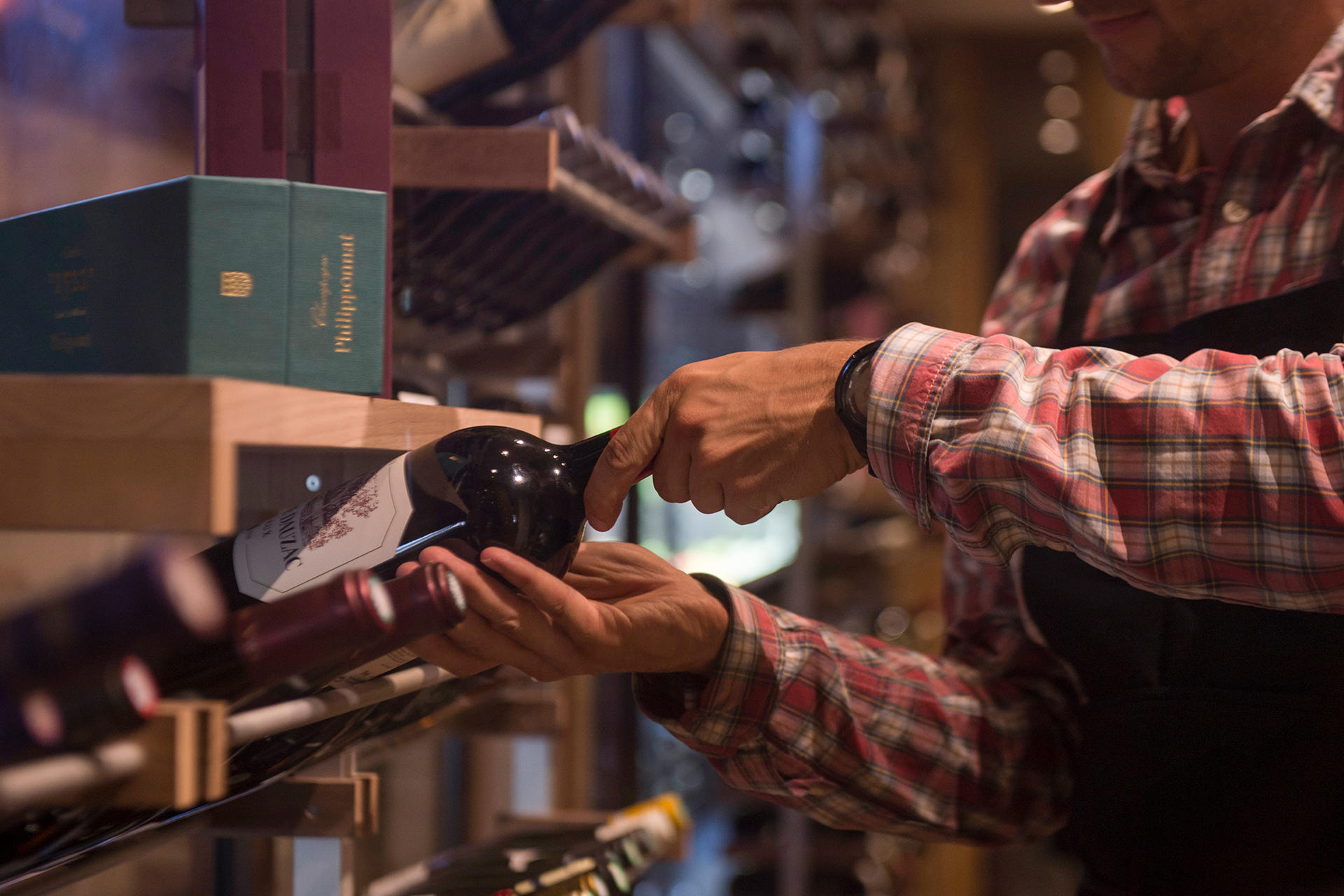 Barman Picking a Bottle of Wine at Hotel Les Gentianettes, The O