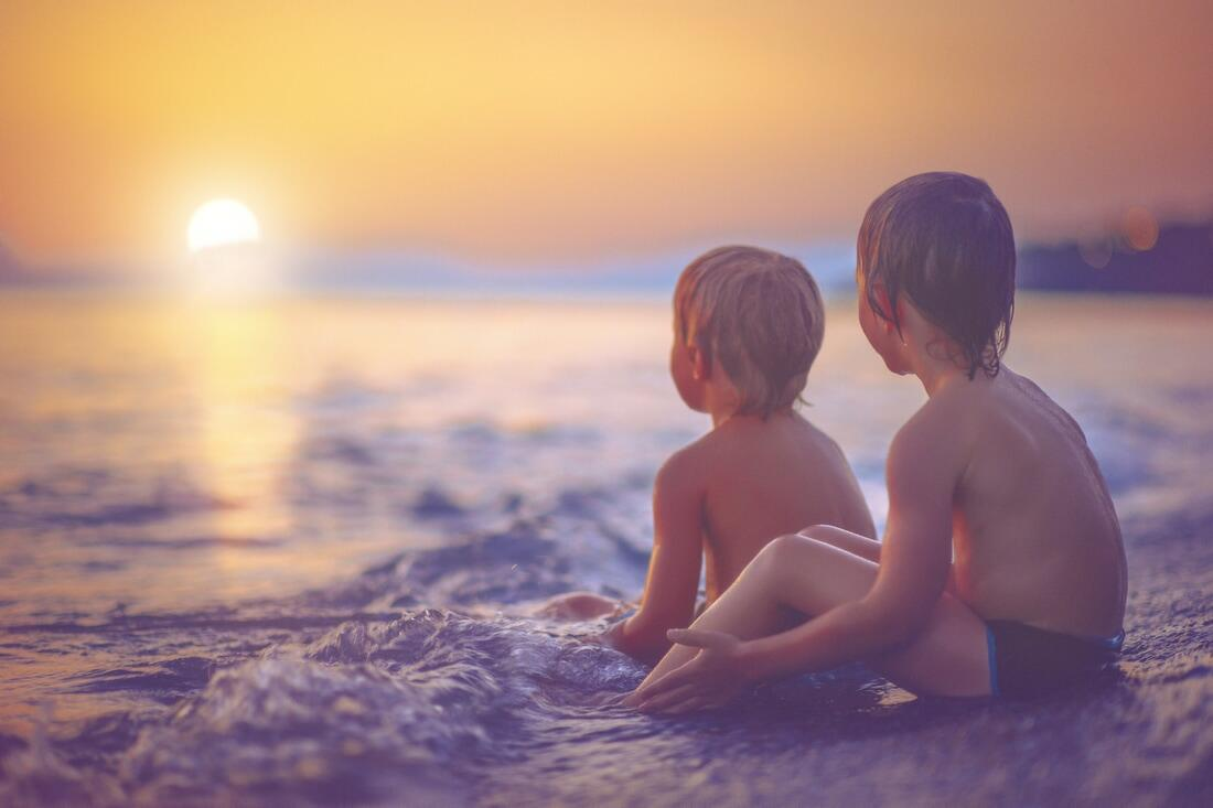 Children on beach at sunset.