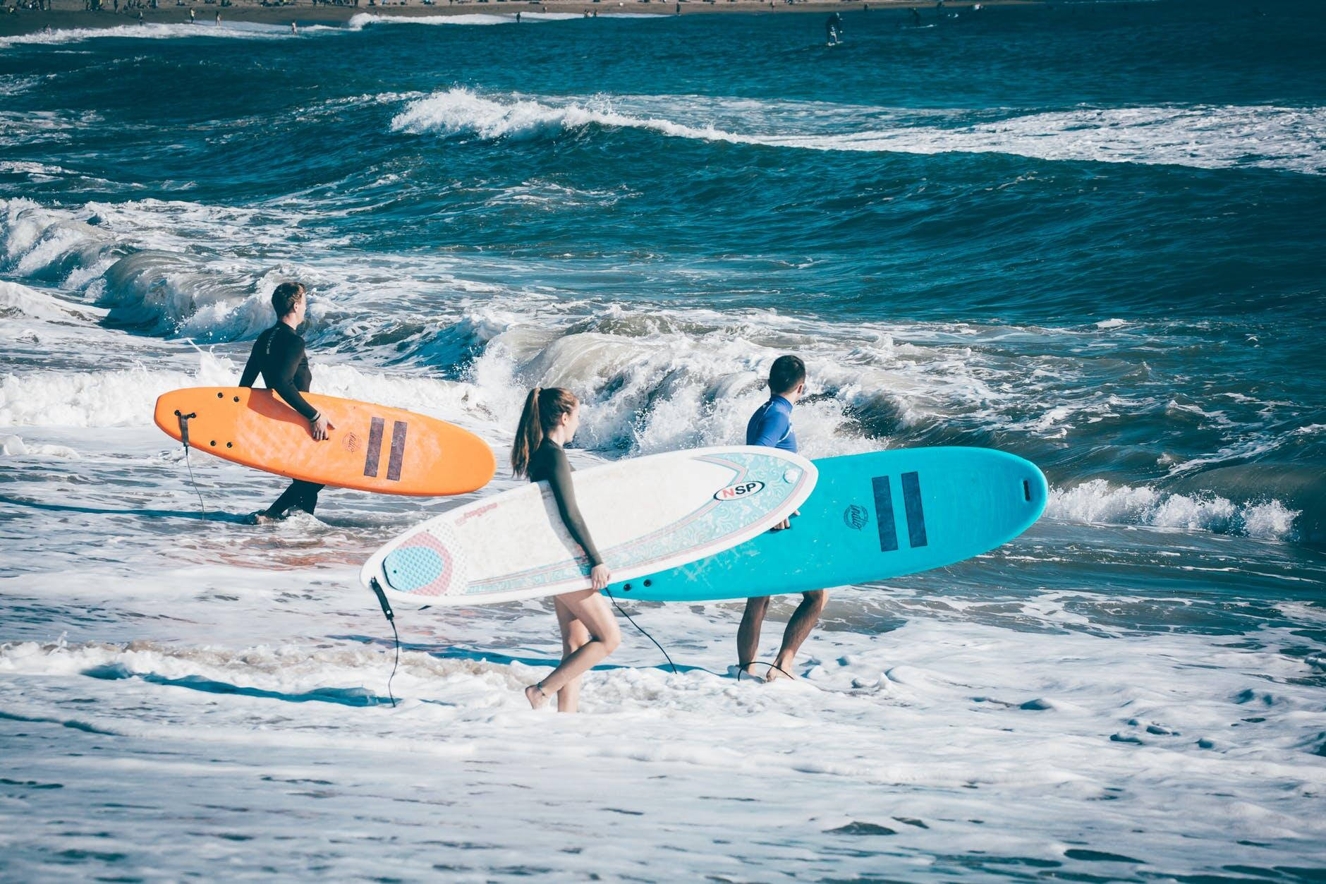 Cluster of beach-goers with surfboards