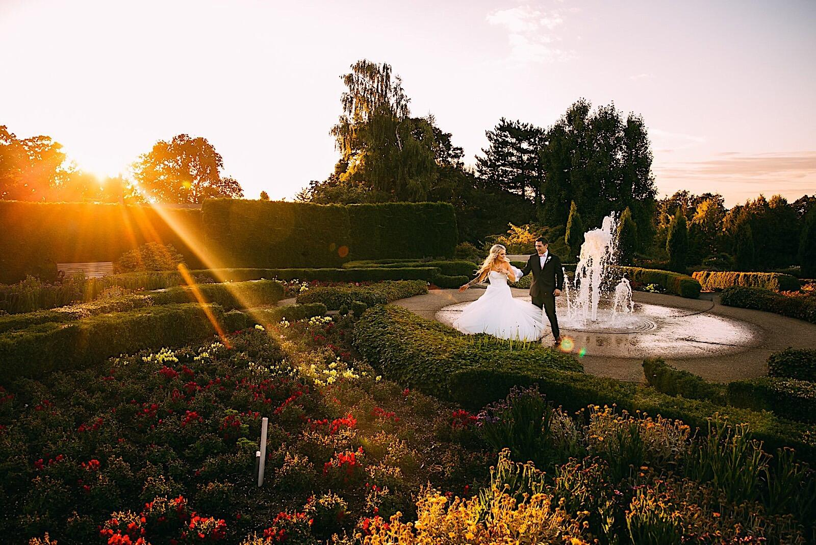 Bride and groom by a fountain in a garden