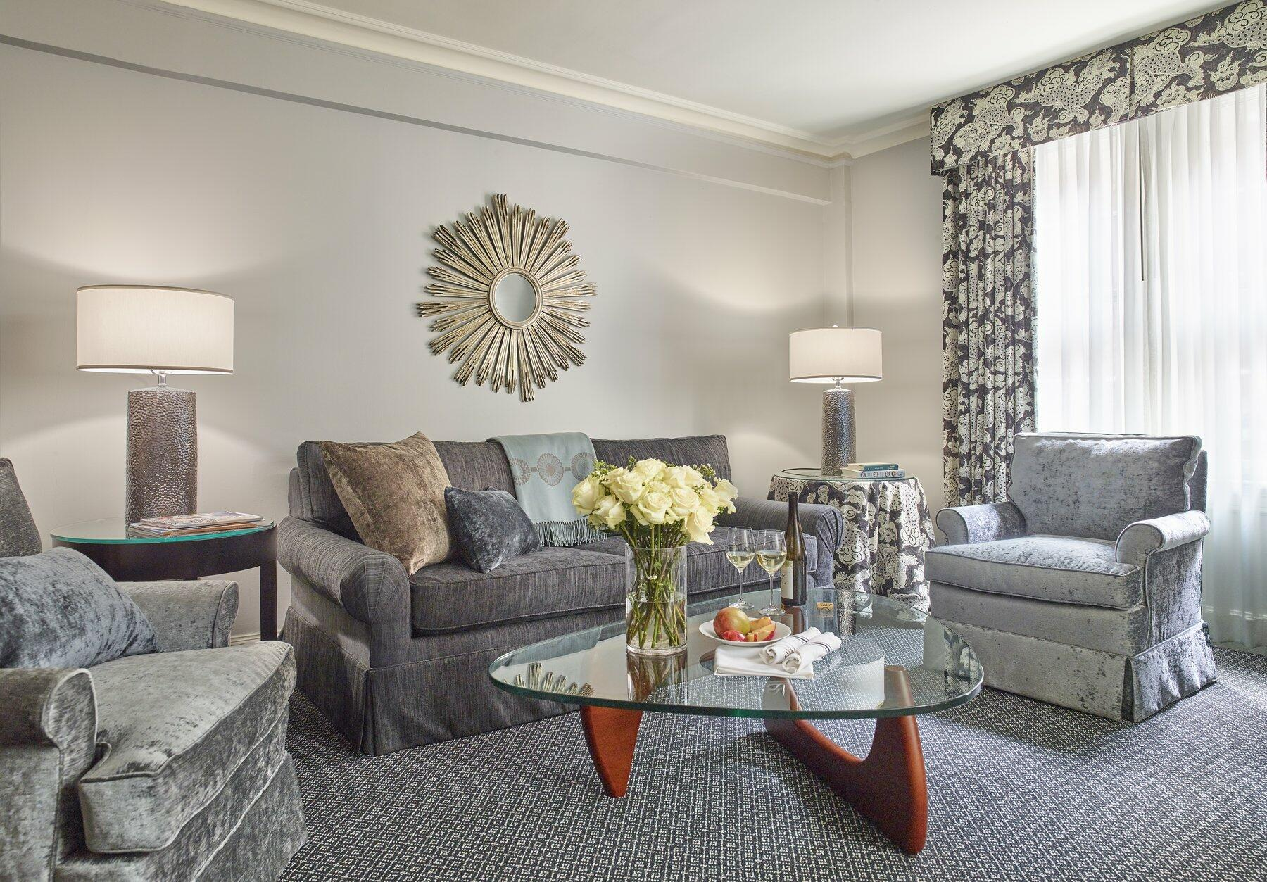 Living room with grey sofa, two chairs and glass coffee table