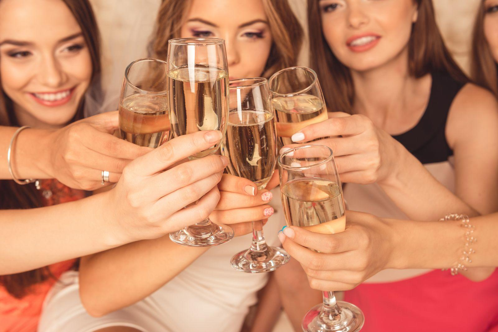 group of women holding up alcohol glasses