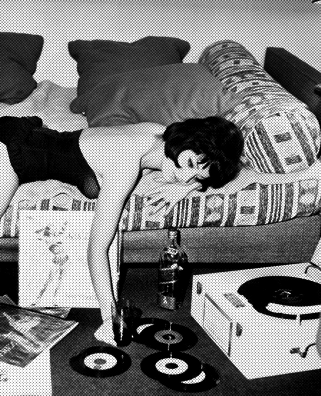 Woman lounging on bed looking at records for record player on fl