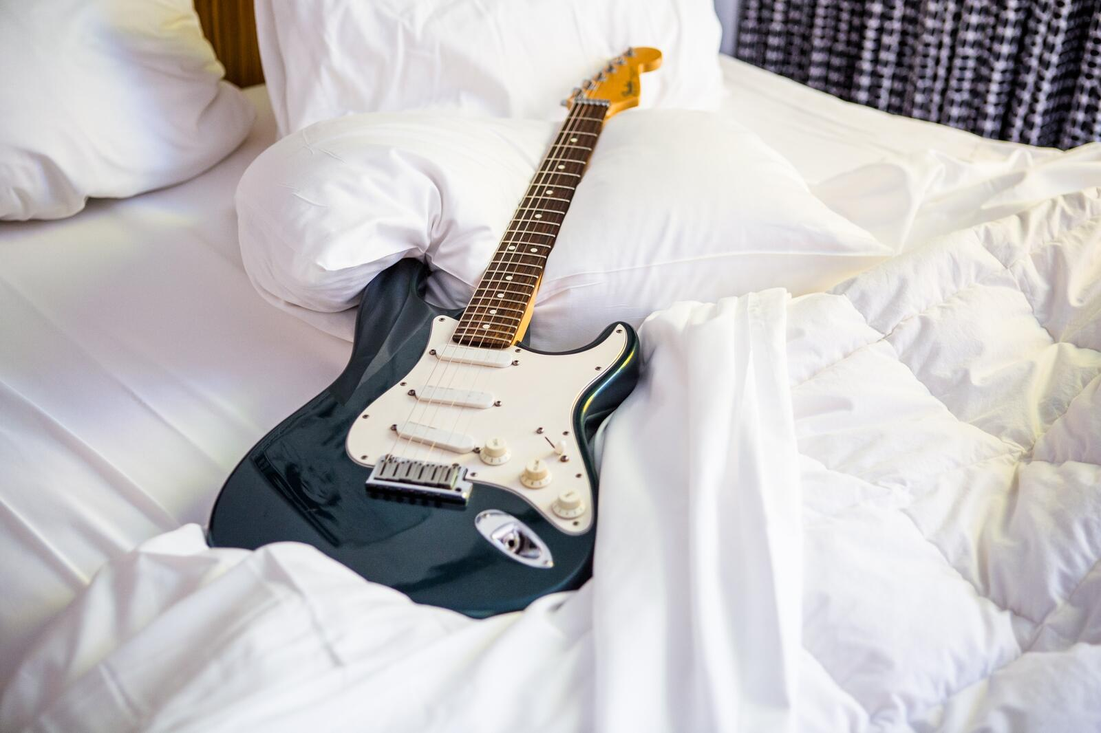 Electric guitar on unmade bed
