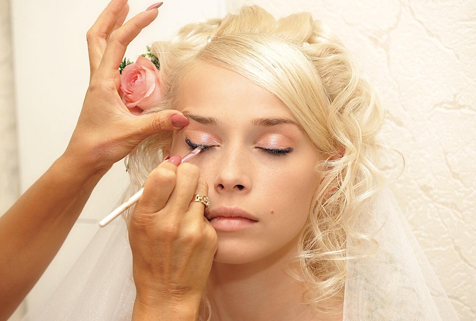 Bride receiving makeup treatment.