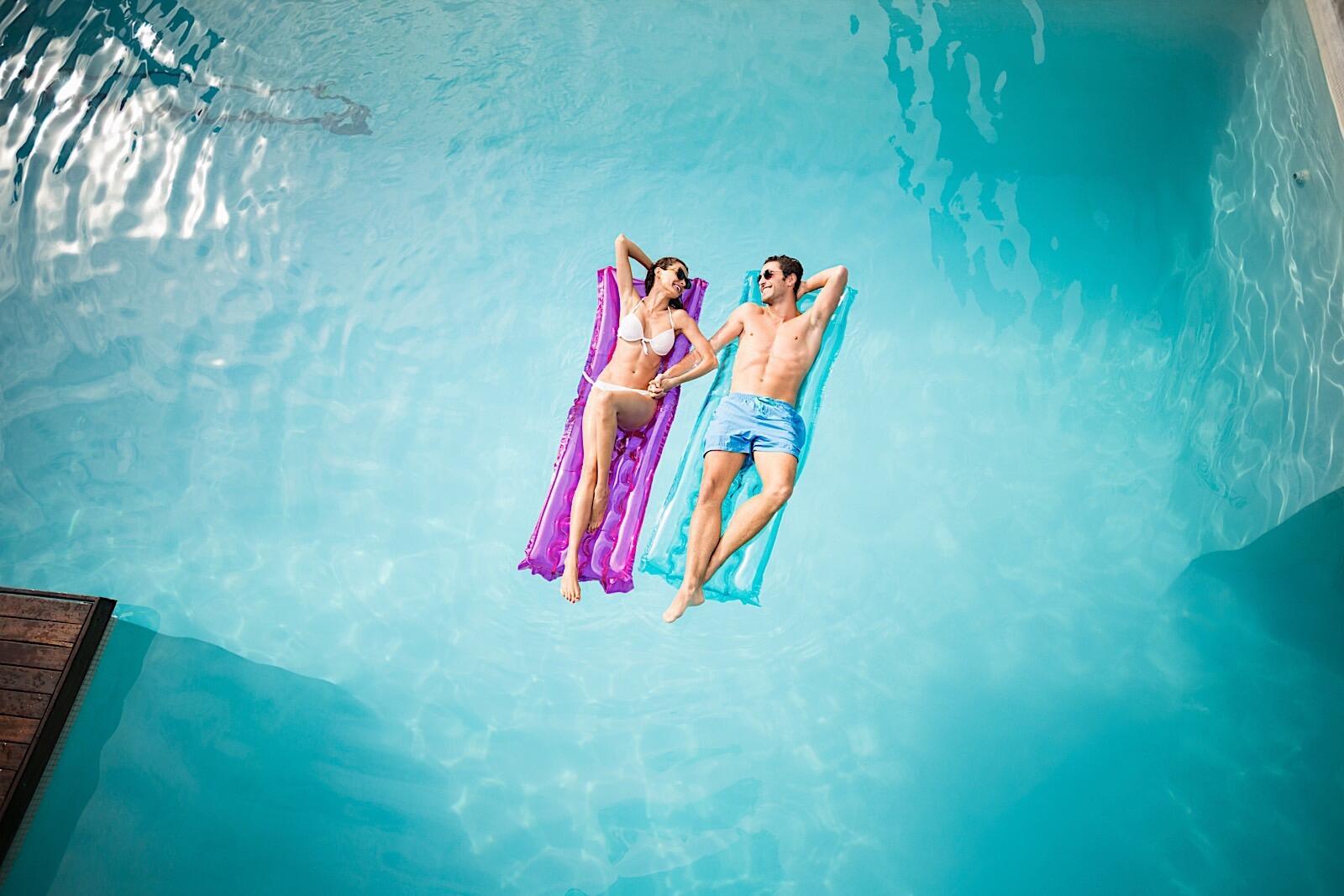 Happy couple floating on pool floats.