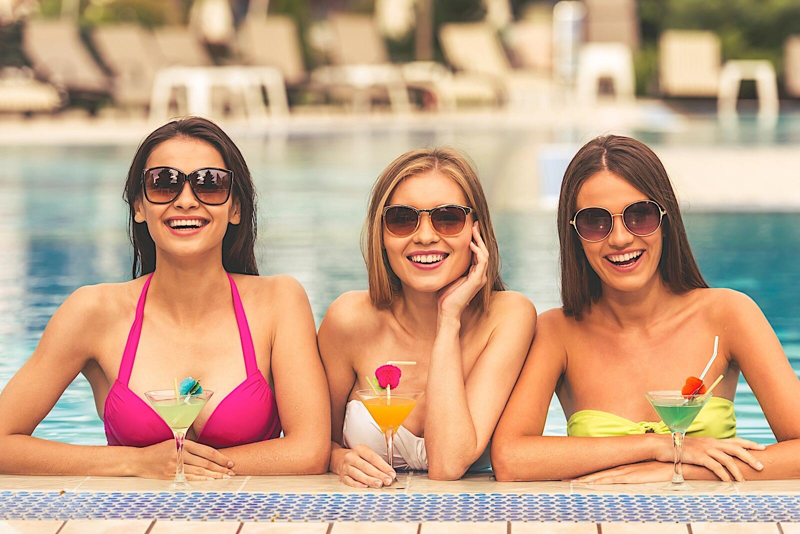 Three friends in an outdoor pool with martini glasses.