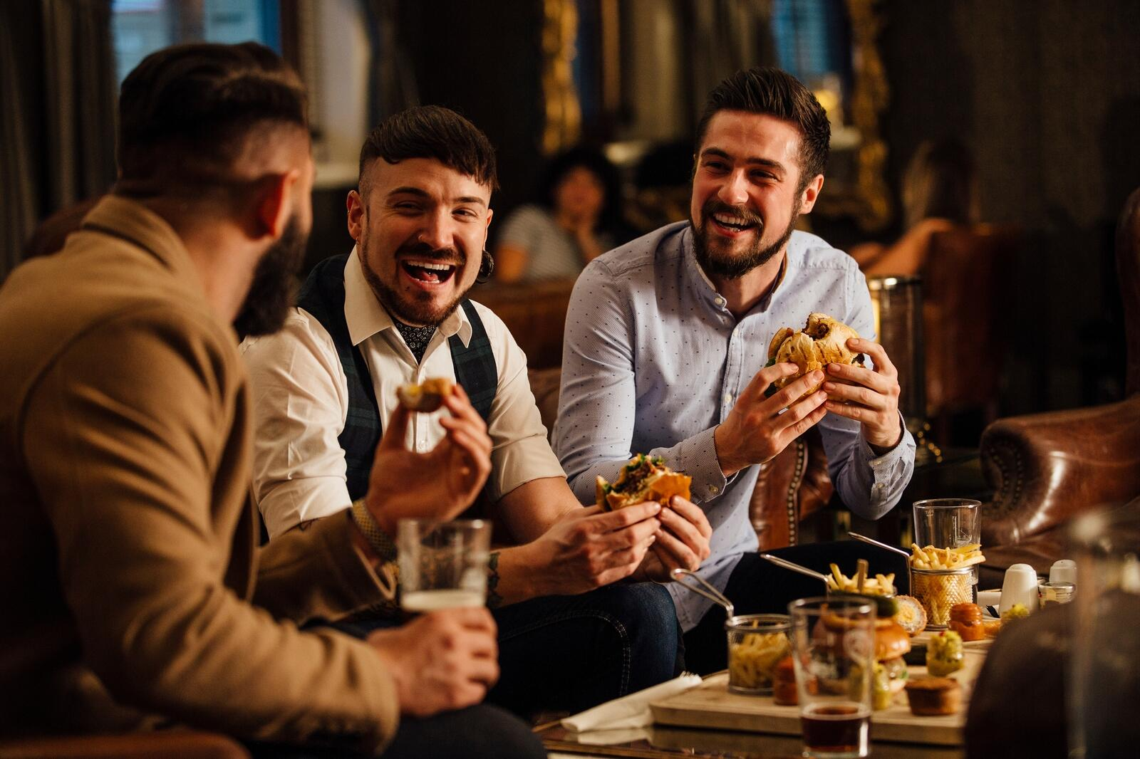 three men laughing while eating burgers and drinking beers
