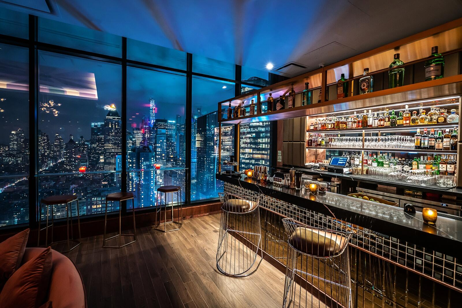 bar with stools and new york city skyline through the windows
