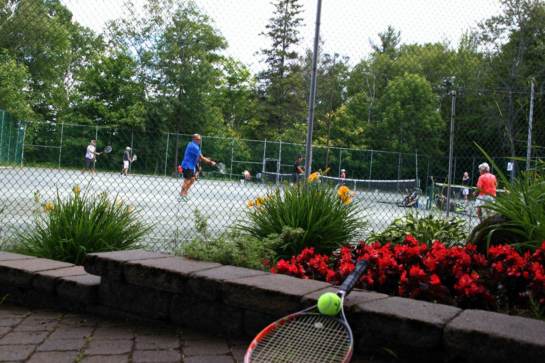 Foreground view of tennis racket with people playing in the back