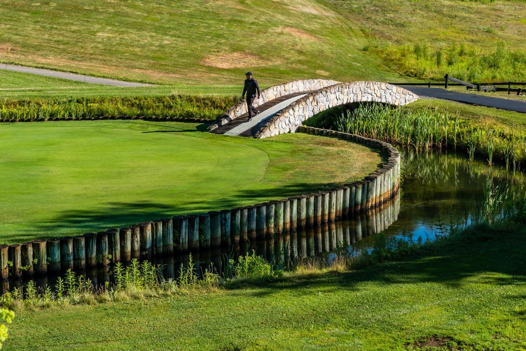Man walking across a stone bridge on a golf course