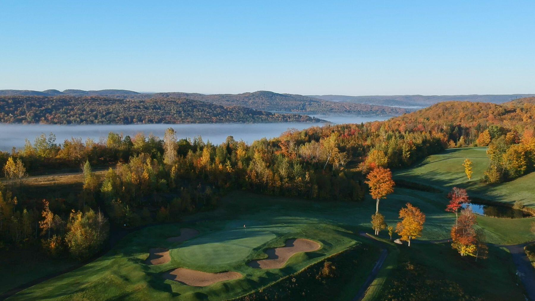 Ariel view of trees leaves changing around golf course