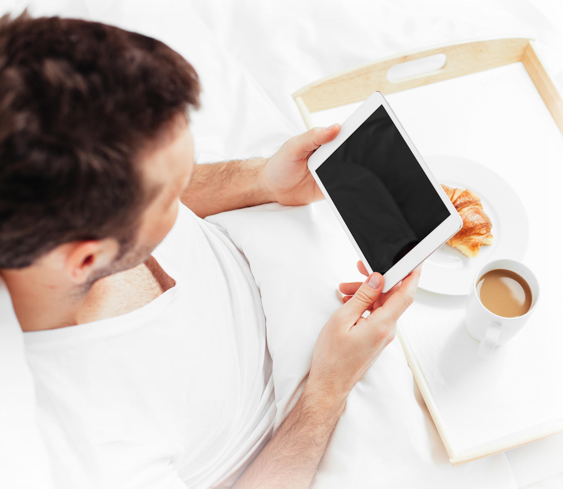 Man watching iPad in bed with coffee & croissant
