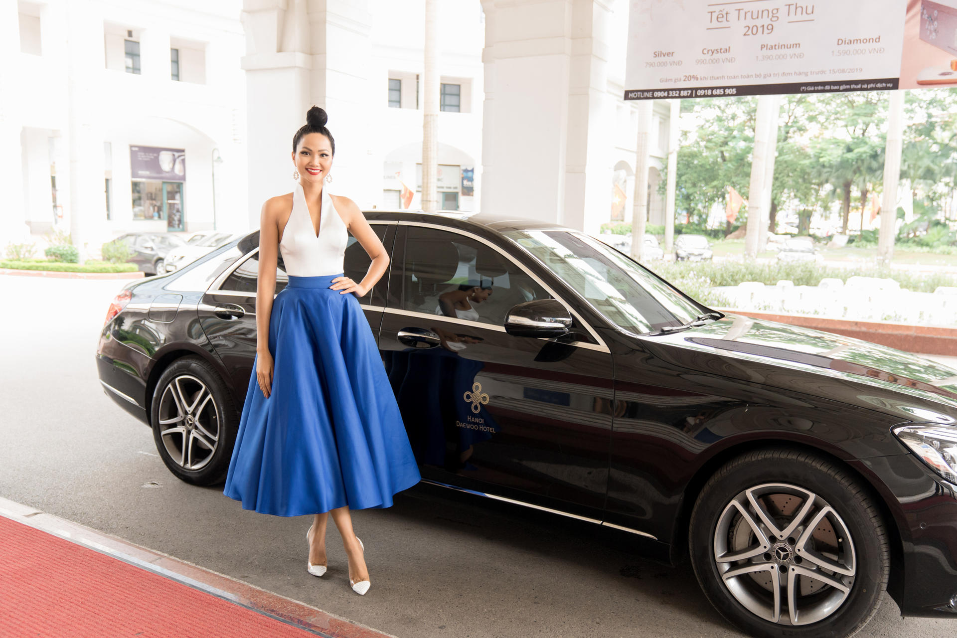 Model posing with a car at entrance of Hanoi Daewoo Hotel