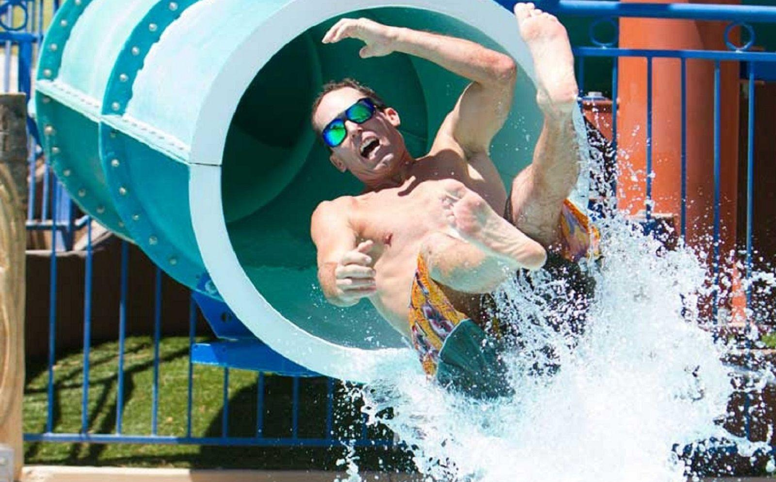 Gentleman exiting a waterslide at high speed.