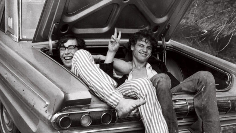 Pair of young men laughing and sitting in the trunk of a classic