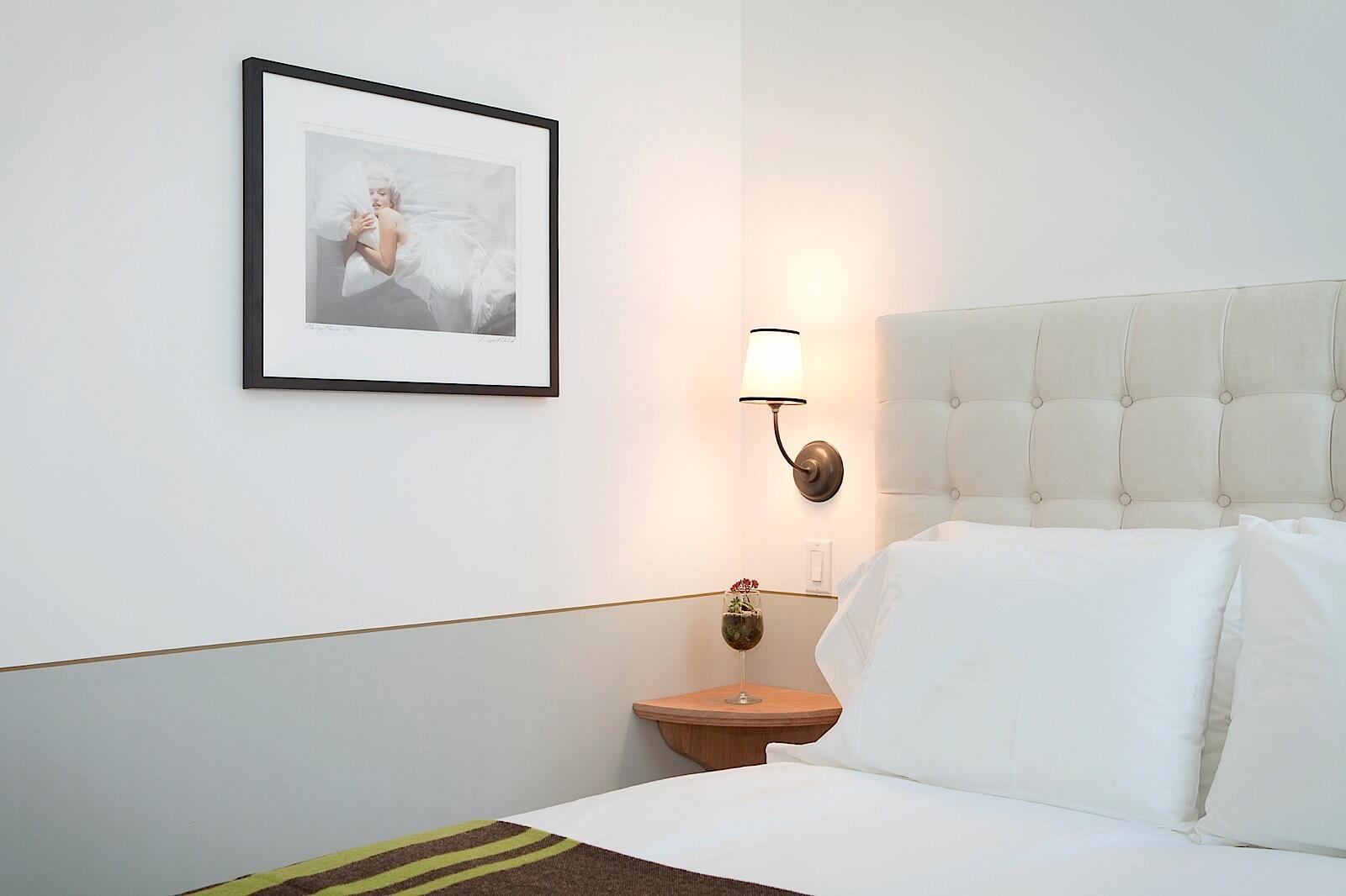 Art on wall and queen bed in Deluxe Queen Room