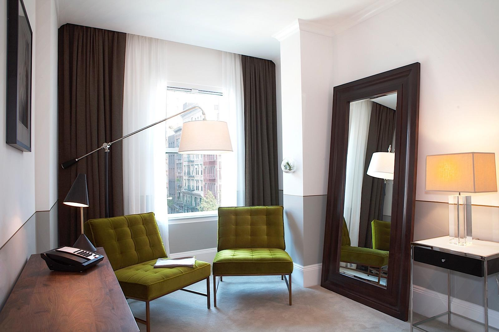 Junior Suite sitting area with large mirror and window