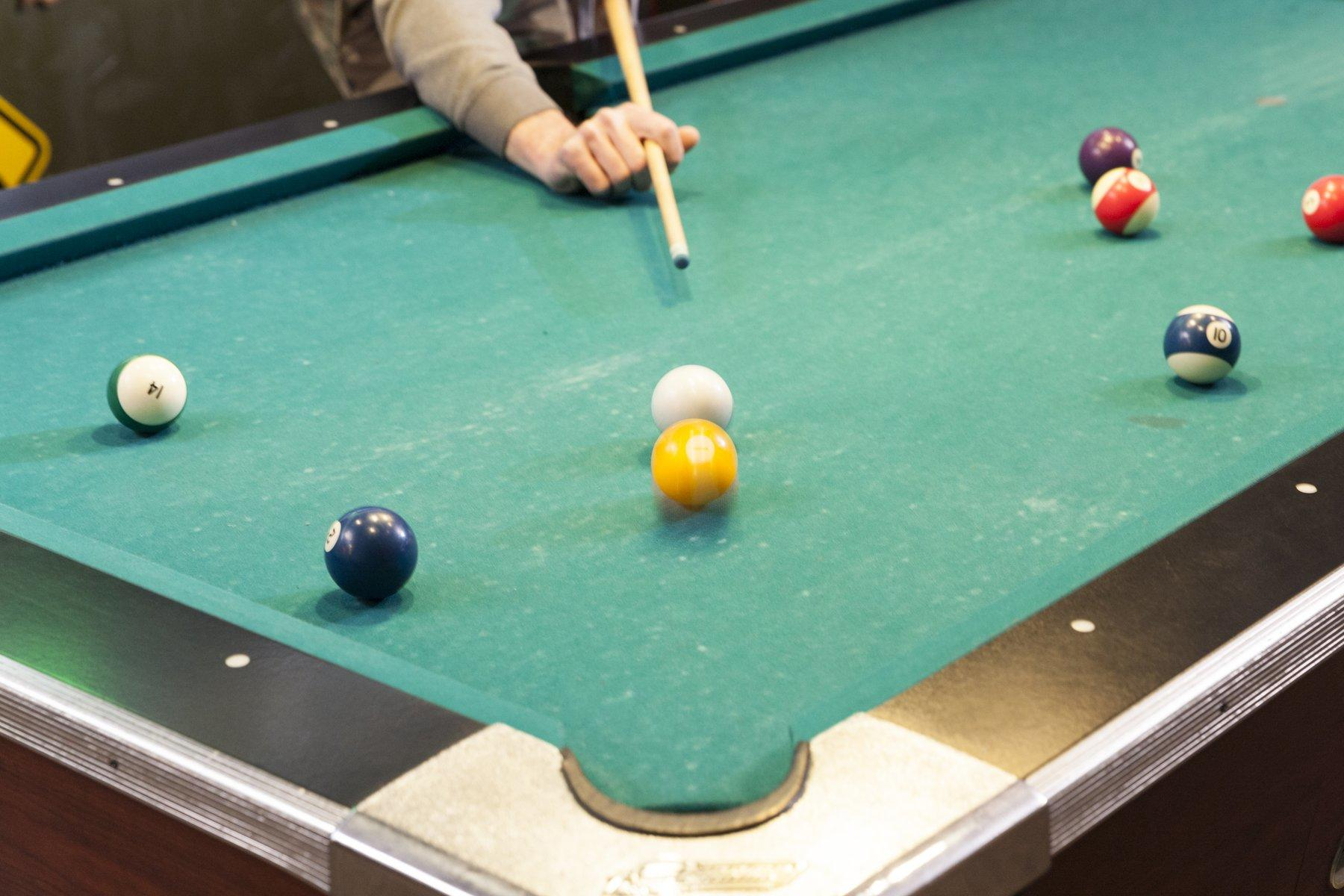 person hitting ball on pool table