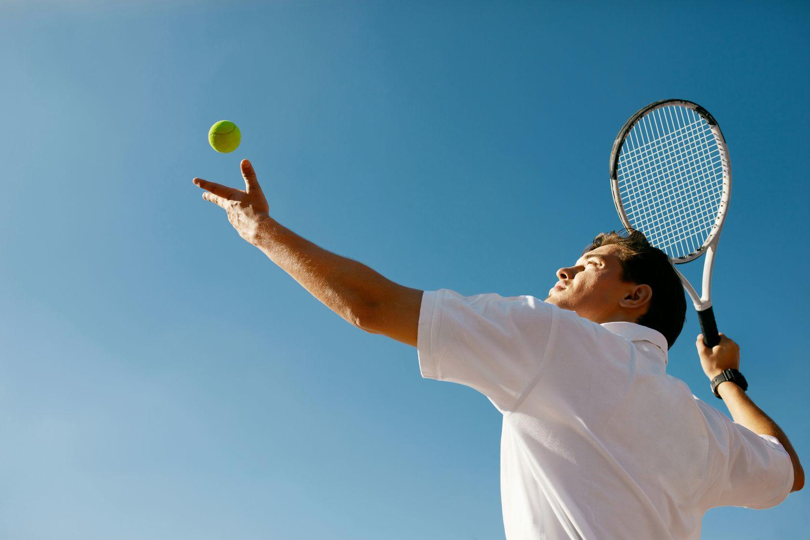 A man in the middle of serving a tennis ball