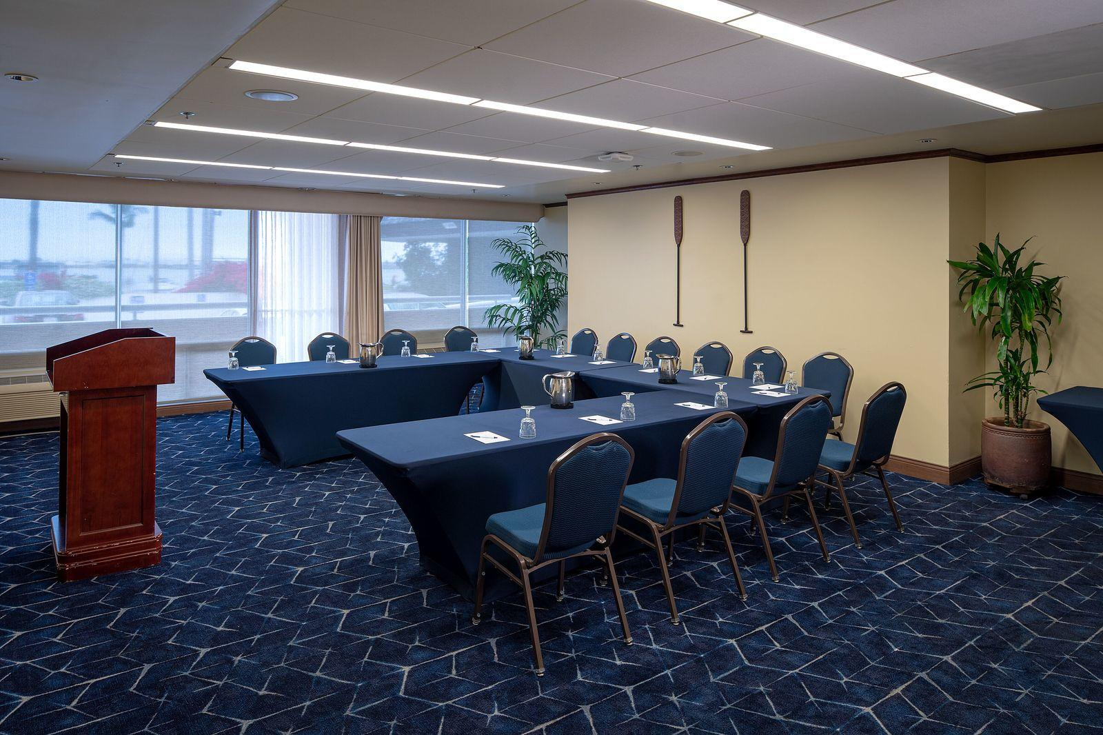 L-shaped desk facing a wooden podium in hotel conference room
