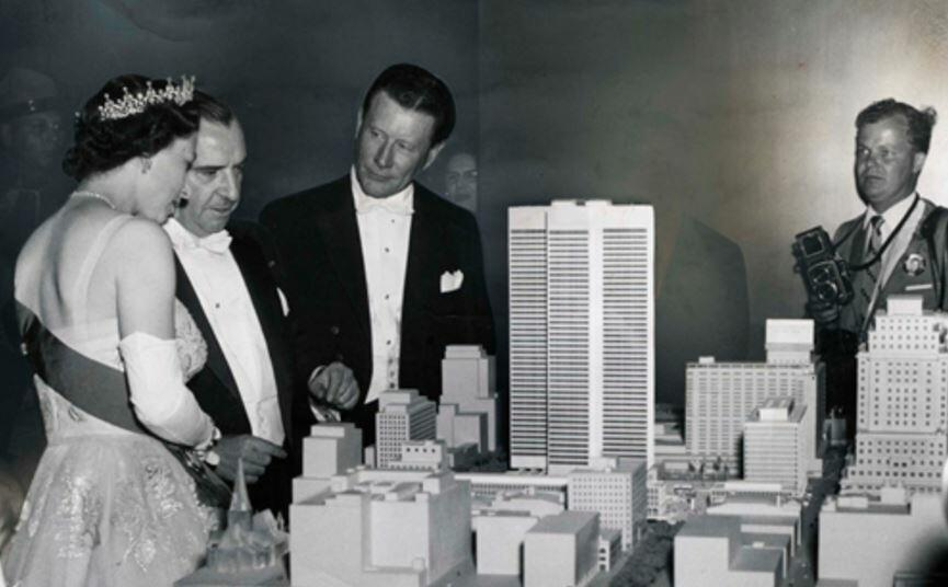 Group of men and women looking at model of city