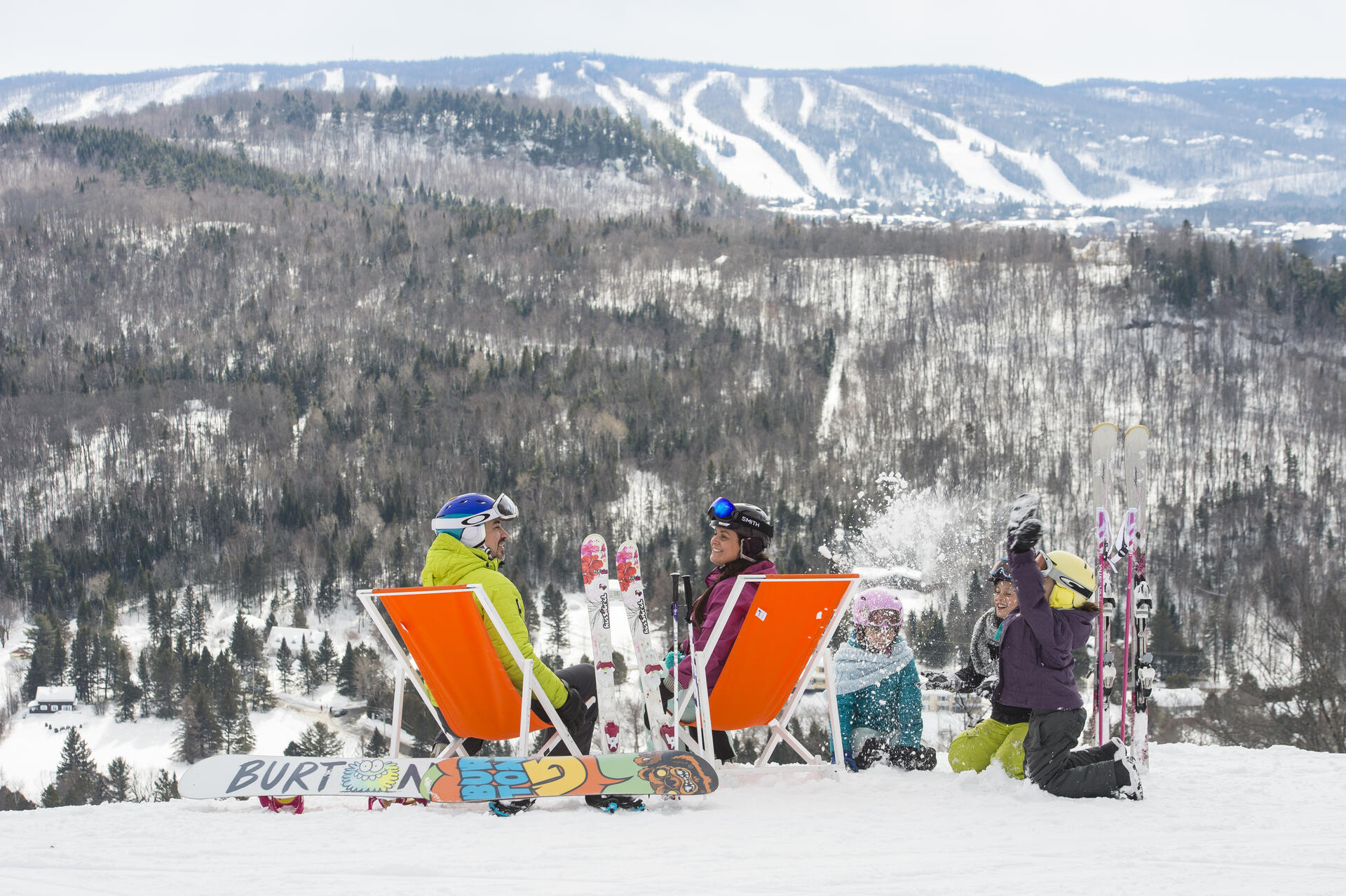 Family relaxing in chairs on snowy mountain