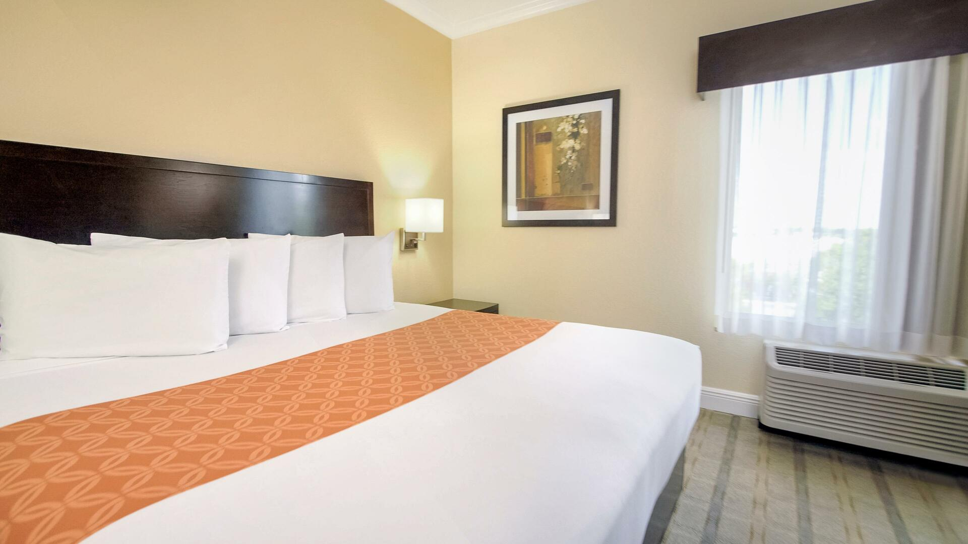 King bed accessible room with plush pillows and windo