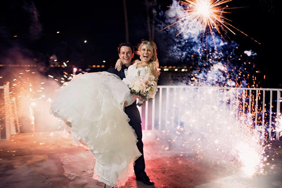 groom holding bride with fireworks in the background