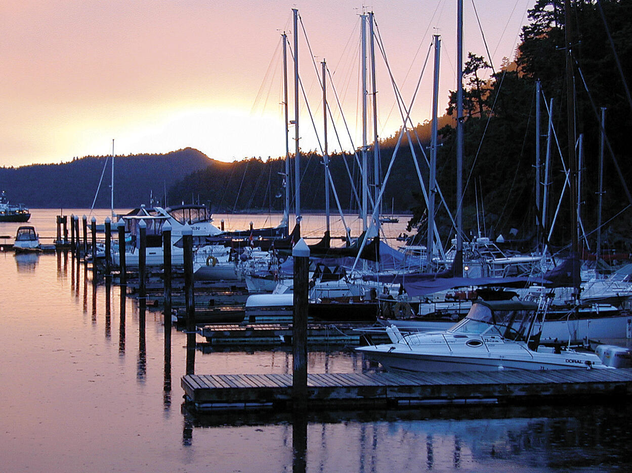 boats in a harbor with sunset in background