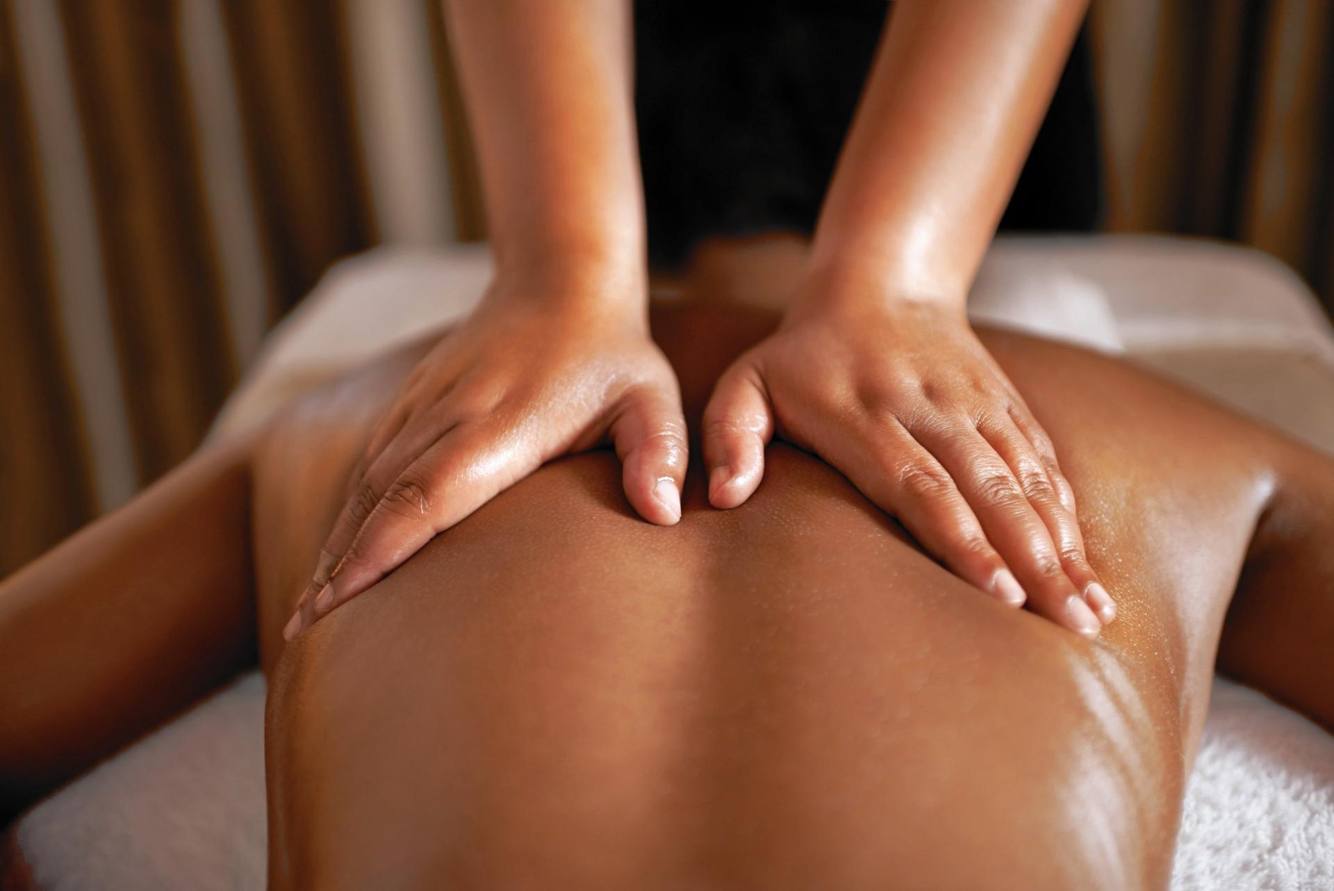 Focus sur les mains de la masseuse qui exerce un massage du dos