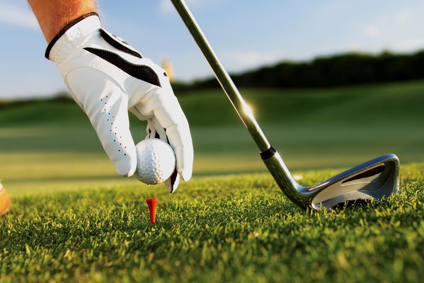 Gloved hand teeing a golf ball.