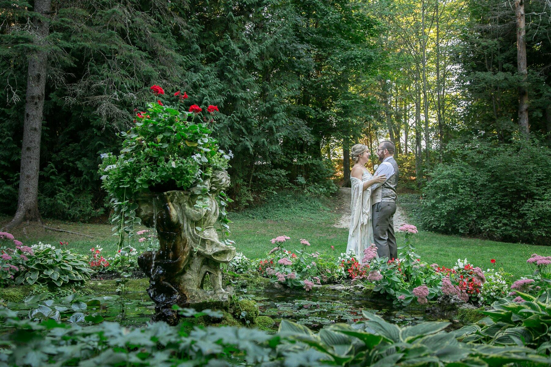 bride and groom posing next to garden