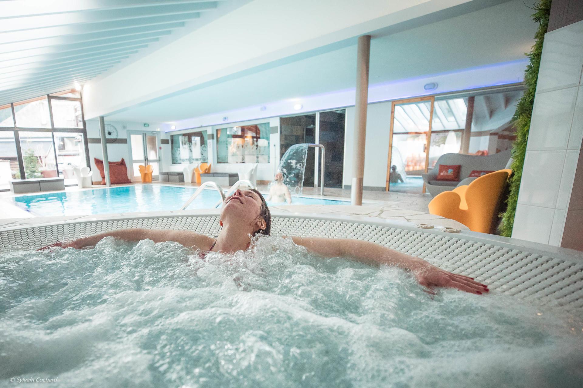 Une femme se relaxant dans le jacuzzi et un homme dans la piscin